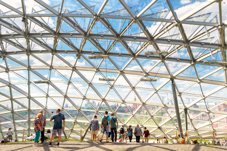Moscow - June 17, 2018: People visit a modern amphitheater with glass dome in Zaryadye Park near Moscow Kremlin in summer, Russia. Zaryadye is one of the main tourist attractions of Moscow.