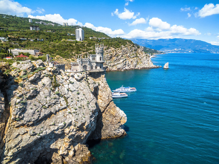 Scenic rocky coastline with castle Swallow's Nest at the precipice in Crimea, Russia. Swallow's Nest is a famous landmark of Crimea. Aerial beautiful view of the Black Sea coast of Crimea in summer. Stock Photo