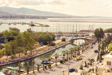 Athens - May 7, 2018: Waterfront in Piraeus, Greece. Scenic aerial view of a beautiful embankment with a canal and marina. Panorama of the city with a sea port. Sunny scenery of the coast of Athens.