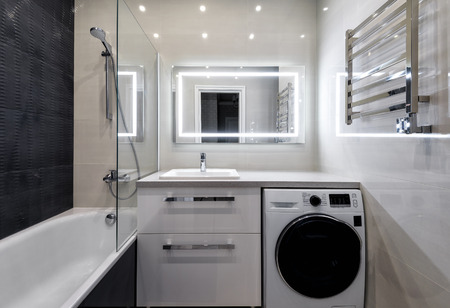 Moscow - June 5, 2018: Interior of bathroom in hotel or residential house. Interior design with light and dark tiles. Modern bathroom with shower, washing machine and LED lighting mirror.