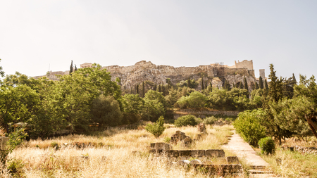 Panoramic view of the Acropolis hill in Athens, Greece. Famous Acropolis is the main tourist attraction of Athens. Scenic panorama of Acropolis with ancient Greek ruins on its top in summer.