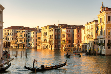 Venice, Italy - May 21, 2017: Gondolas floats on the Grand Canal in Venice at sunset. Gondola is the most attractive tourist transport in Venice. Romantic water trip across Venice city in evening.