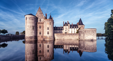 Castle or chateau de Sully-sur-Loire at dusk, France. This medieval castle is a famous landmark in Loire Valley. Panoramic view of the old castle on the water. Strong French vintage castle in evening.