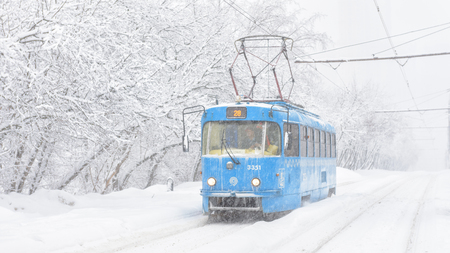 Moscow - Feb 4, 2018: Tram goes during snowstorm in winter, Russia. Cold and snowfall in the city. Panoramic view of the Frozen tram on a snowy street.