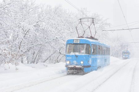 Moscow - Feb 4, 2018: Trams go during snowstorm in winter, Russia. Cold and snowfall in the city. Frozen tram on the snowy street. Editorial