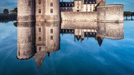 Castle or chateau de Sully-sur-Loire in evening, France. This medieval castle is a landmark of Europe. Panorama of old French castle with reflection in the water. View of the vintage castle at dusk.