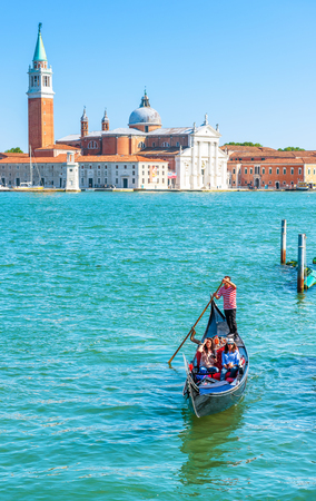 Venice - May 18, 2017: Gondola sails against the San Giorgio island in Venice, Italy. Gondola is the most attractive tourist transport in Venice. Concept of traveling and vacation in sunny Venice. Editorial