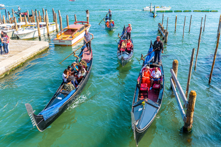 Venice - May 18, 2017: Gondolas sail near the San Marco Square in Venice, Italy. Gondola is the most attractive tourist transport in Venice. Concept of traveling and vacation in sunny Venice.