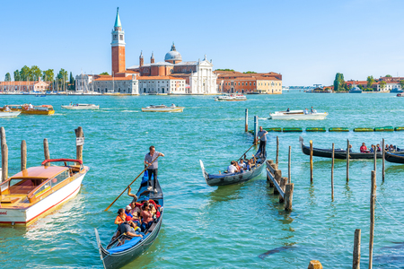 Venice - May 18, 2017: Gondolas sail near the San Marco Square in Venice, Italy. Gondola is the most attractive tourist transport in Venice. Concept of traveling and vacation in summer Venice.