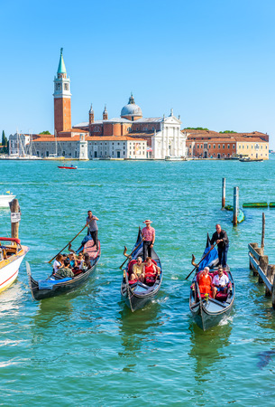 Venice - May 18, 2017: Gondolas sail against the San Giorgio island in Venice, Italy. Gondola is the most attractive tourist transport in Venice. Concept of traveling and vacation in sunny Venice.