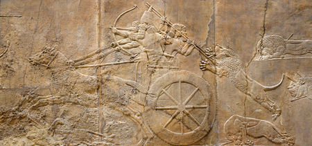 Assyrian wall relief of the royal lion hunt. Ancient carving panoramic panel from Middle East history. Remains of the culture of ancient civilization. Assyrian and Sumerian art for vintage background.