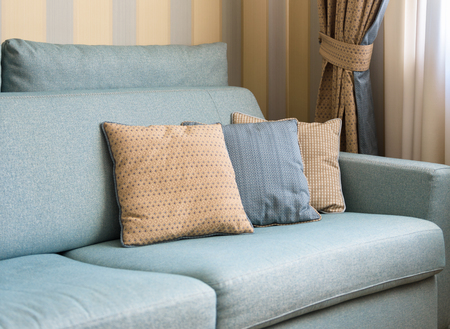 Couch or sofa with cushions in the home interior. Classic couch pillows close-up. Detail of the pastel interior of flat in daylight. Stockfoto