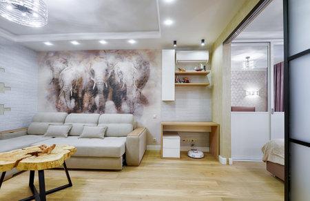Moskau - 6. Dezember 2018: Moderne Inneneinrichtung mit Fresko. Helle Innenarchitektur von Wohnzimmer und Schlafzimmer. Panorama des stilvollen weißen Interieurs der Wohnung mit einer schönen bemalten Wand. Editorial