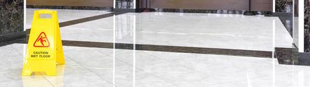 Piso de mármol brillante en un pasillo de lujo de una empresa u hotel durante la limpieza. Panorama de un piso limpio lavado con signo de precaución piso mojado. Servicio de atención profesional del interior de la oficina.