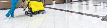 Bodenpflege mit Waschmaschine in einer Bürolobby. Panorama des Reinigungsservice mit Vakuumausrüstung auf glänzendem Marmorboden im luxuriösen Interieur des Unternehmens. Konzept der professionellen Reinigungsarbeit. Standard-Bild