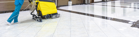 Floor care with washing machine in an office lobby. Panorama of cleaning service with vacuum equipment on shiny marble floor in the luxury interior of company. Concept of professional cleaning job. Stock fotó