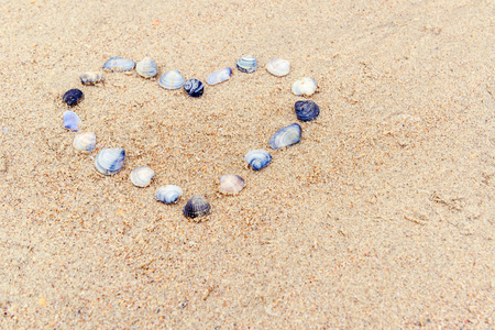 Heart built of sea shells on the sand. Romantic symbol of love made on a beach in summer. Small seashells lie in the shape of the heart for background. Concept of tropical travel and vacation. Imagens