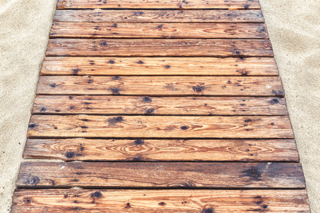 Wooden pathway on a sandy beach in summer. Natural wood planks background. The tourist track with an old decking to sea close-up. Top view of footpath paved with vintage wood boards.