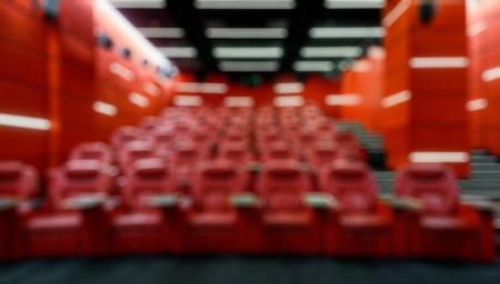 Panoramic view of an empty cinema hall as creative abstract blur background. Inside the red comfortable theatre. Contemporary cinema auditorium design. Panorama of the modern movie theater interior.