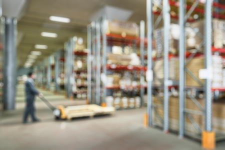 Panorama of warehouse interior as abstract blur background. Worker with fork pallet truck stacker works in storehouse. Logistics and transportation concept. People work inside modern storehouse.