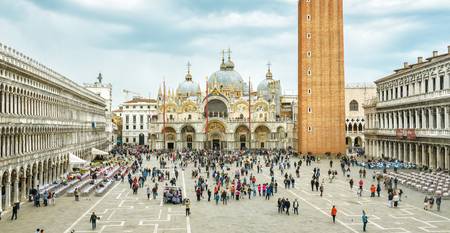 Venice, Italy - May 20, 2017: Piazza San Marco or St Marks Square in Venice. It is a top tourist attraction of Venice. Panoramic view of the famous Venice center in summer. People walk near Basilica.