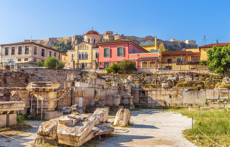 Library of Hadrian overlooking Acropolis and beautiful houses at old Plaka district, Athens, Greece. It is a famous landmark of Athens. Scenic panorama of Ancient Greek ruins in the Athens center. Stock Photo