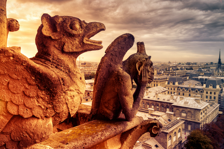 Gargoyles or chimeras on the Notre Dame de Paris overlooking Paris, France. Old cathedral of Notre Dame is a famous landmark of Paris. Dramatic view of Paris with the vintage demon statues on fire.