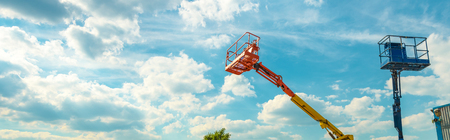 Cherry pickers on blue sky background. Boom with lift buckets of heavy machinery. Panoramic view of the platforms of the telescopic construction lifts in summer. 写真素材