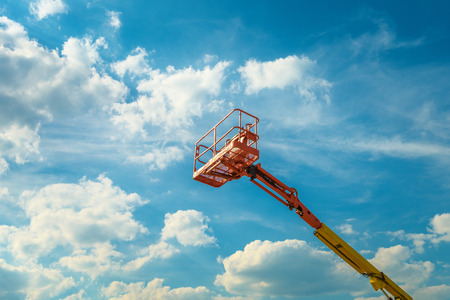 Cherry picker on the blue sky background. Boom with lift bucket of heavy machinery. View of the platform of the telescopic construction lift in summer.