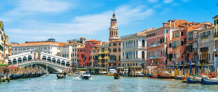 Rialto-Brücke über den Canal Grande, Venedig, Italien. Es ist ein berühmtes Wahrzeichen von Venedig. Panorama der Altstadt von Venedig im Sommer. Stadtbild von Venedig mit bunten Häusern und Touristenbooten an einem sonnigen Tag. Standard-Bild