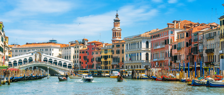 Rialto Bridge over Grand Canal, Venice, Italy. It is a famous landmark of Venice. Panorama of the old Venice city in summer. Cityscape of Venice with colorful houses and tourist boats on sunny day. Stockfoto
