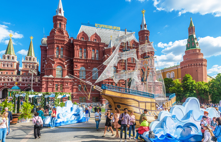 Moscow – May 19, 2019: People walk on Manezhnaya Square by Moscow Kremlin, Russia. This place is a tourist attraction of Moscow. Festive decorations near landmarks in the Moscow city center in summer. Editorial