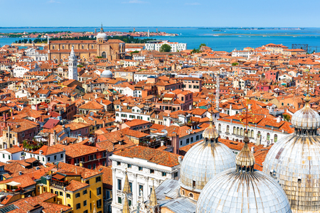 Venice taken from above, Italy. Cityscape with domes of St Mark`s Basilica. Beautiful Venice skyline. Aerial panoramic view of the Venice city in summer. Mediterranean urban landscape on sunny day.