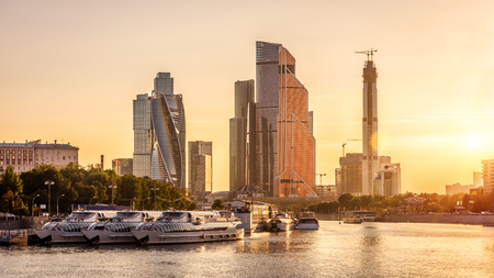 Panorama of Moscow with modern skyscrapers of Moscow-City at sunset, Russia. Sunny view of Moskva River and moored tourist ships in the Moscow center in summer. Moscow cityscape with tall buildings. Stock Photo