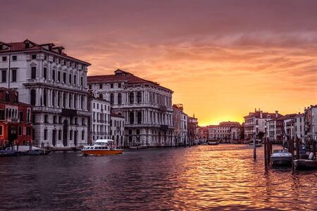 Venice at sunset, Italy. Panorama of Grand Canal in evening. Urban landscape of Venice in sun light. Beautiful sunny view of the Venice city at dusk. Romantic water trip across Venice in twilight.