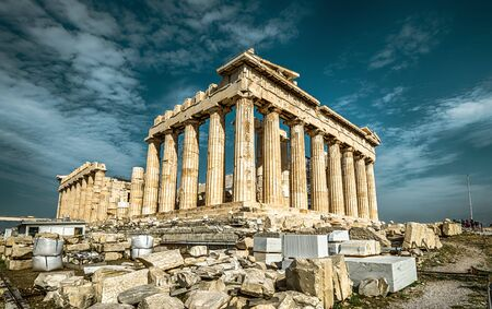 Parthenon on the Acropolis of Athens, Greece. Ancient Greek Parthenon is a top landmark of Athens. Dramatic view of remains of the antique Athens city. Panorama of the famous temple ruins in summer.