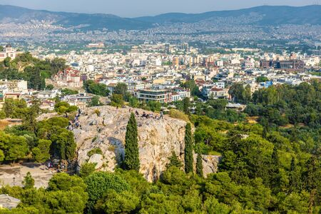 Panorama of Athens from the Acropolis, Greece. Areopagus rock with people in foreground. It is one of the main tourist attractions of Athens. Scenic view of the Athens city. Urban landscape in summer. Stock Photo