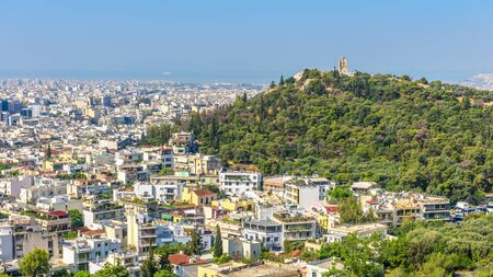 Panorama of Athens with Philopappu or Muse Hill, Greece. It is a tourist attraction of Athens. Scenic view of the Athens city from the famous Acropolis. Urban landscape in summer. Athens skyline.