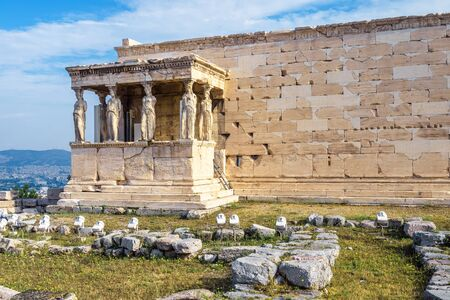 Erechtheion temple with Caryatid Porch on the Acropolis, Athens, Greece. Famous Acropolis hill is a main landmark of Athens. Ancient Greek ruins in Athens center. Remains of antique Athens in summer.
