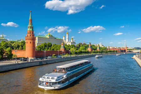 Moscow center in summer, Russia. Famous Moscow Kremlin is a top tourist attraction of city. Scenic view of the Moscow landmark and ship on Moskva River. Concept of travel and vacation in Moscow. 스톡 콘텐츠