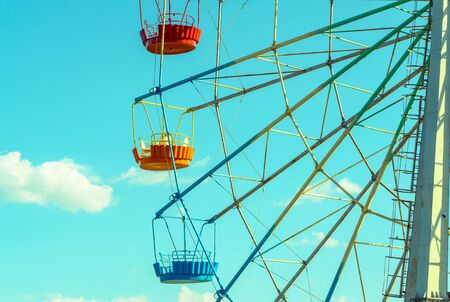 Ferris wheel with colorful cabins on the blue sky background. Detail of the colored Ferris wheel against clouds. Concept of holiday and kids amusement.