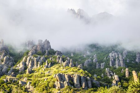 Mountain landscape with fog, Crimea, Russia. Valley of Ghosts of misty Demerdji mountain. This place is a natural tourist attraction of Crimea. Scenic view of bizarre rocks in haze or low clouds. Banco de Imagens
