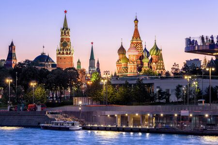 Moscow Kremlin and St Basil`s Cathedral at night, Russia. Zaryadye Park on embankment of Moskva River. Beautiful panorama of the Moscow city center at dusk. Evening view of the Moscow landmarks.