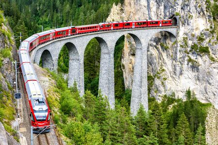 Landwasser Viaduct in Filisur, Switzerland. It is famous landmark of Swiss. Red express train on high bridge in mountains. Scenic view of amazing railway in summer. Concept of travel in Alpine Europe. Banco de Imagens