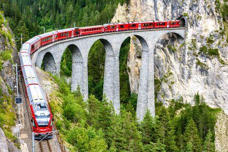 Viaduc de Landwasser à Filisur, Suisse. C'est un monument célèbre de la Suisse. Train express rouge sur le pont élevé dans les montagnes. Vue panoramique sur le chemin de fer incroyable en été. Concept de voyage en Europe alpine.