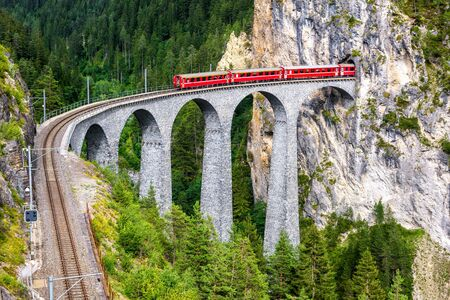 Landwasser Viaduct in Filisur, Switzerland. It is a famous landmark of Swiss Alps. Red express train on high bridge in mountains. Scenic view of amazing railway in summer. Concept of travel in Europe.