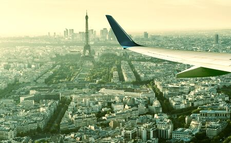 Plane flies above Paris, France. Aerial panoramic view of Eiffel tower from airplane window. The plane's wing over streets of Paris. Concept of air travel to Paris. Flight in Europe in summer. Zdjęcie Seryjne - 129212587