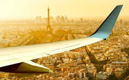 Plane flies above Paris in summer evening, France. Aerial panoramic view of Eiffel tower from airplane window. The planes wing over streets of Paris at sunset. Flight and air travel to Paris.