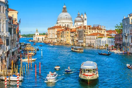 Venice, Italy - May 18, 2017: Panorama of Grand Canal in summer Venice. Tourist boats and ships sail on main street in the Venice old center. Concept of travel and vacation in sunny Venice city.