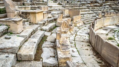 Theatre of Dionysus at the foot of Acropolis, Athens, Greece. It is one of the top landmarks in Athens. Detail of the famous outdoor theatre with stone seats. Ancient Greek ruins in Athens center.